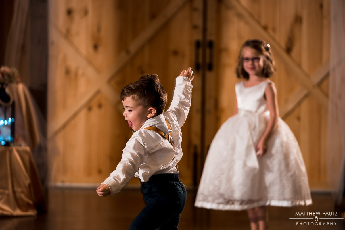 Ring bearer dancing with flower girl at windy hill barn reception