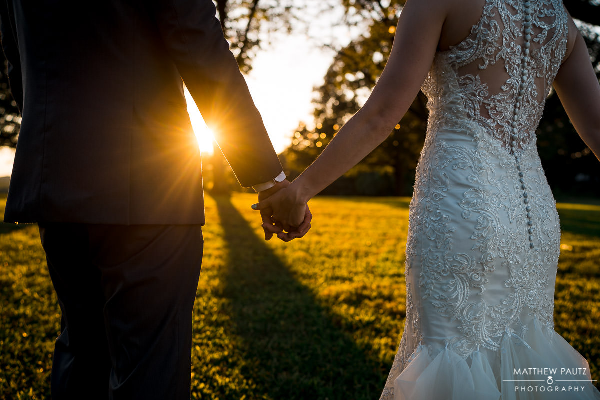 newlywed couple holding hands during sunset
