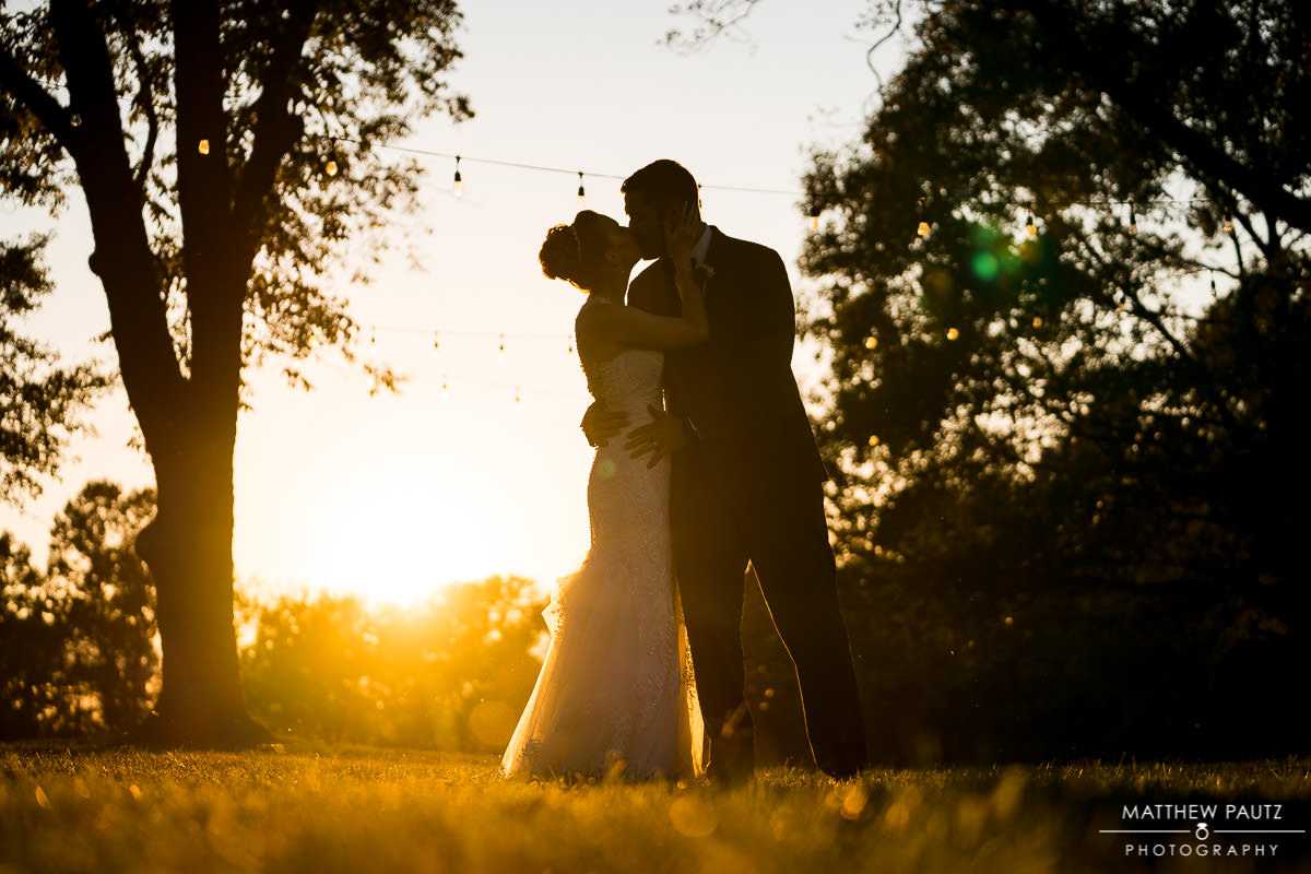 silhouette of bride and groom kissing at sunset
