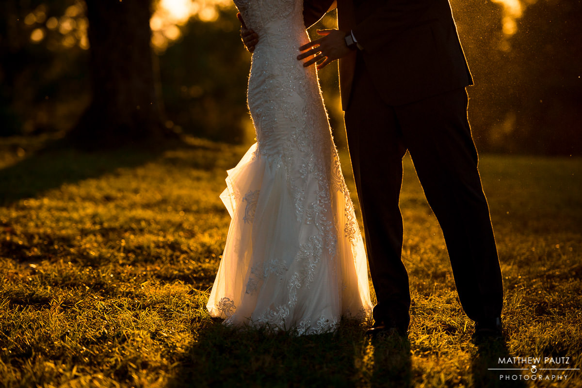 closeup of bride and groom hugging at sunset