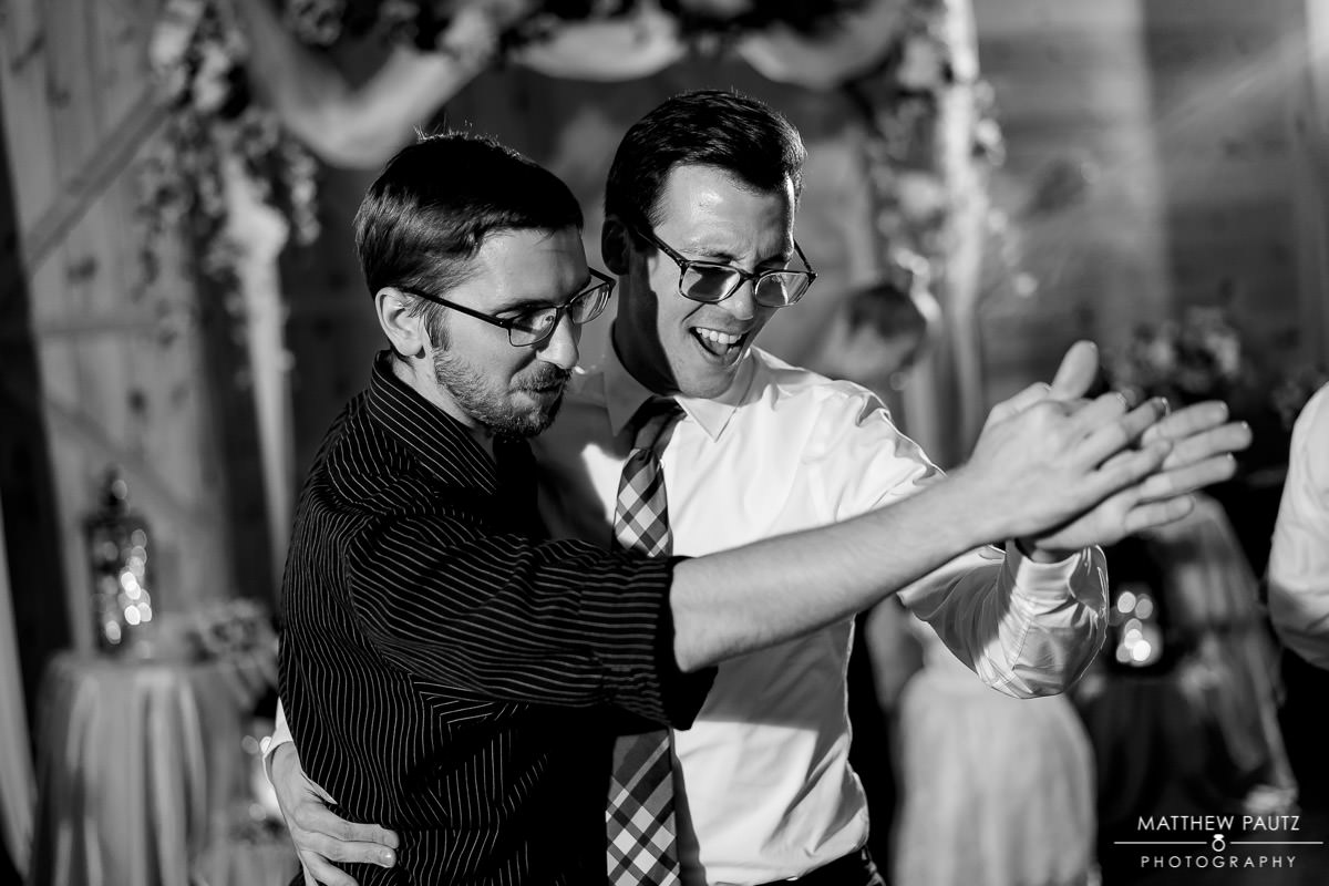 Two wedding guests dancing together at reception