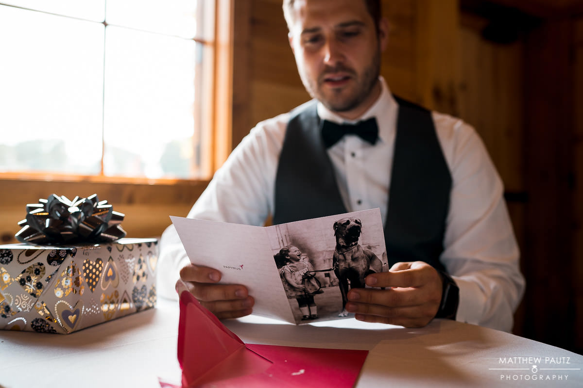 Groom reading card before wedding