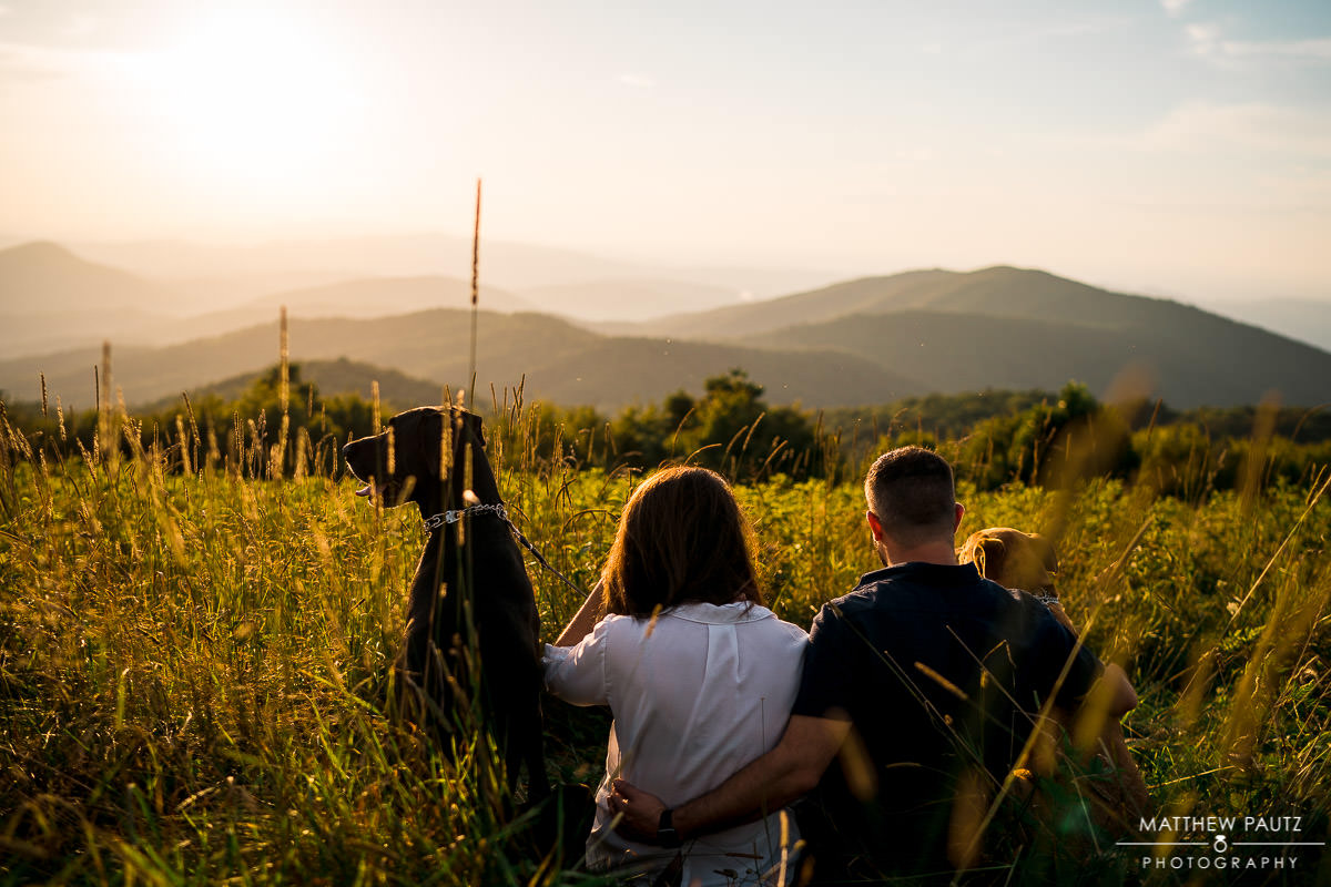 couple sitting in tall grass enjoying a mountain view