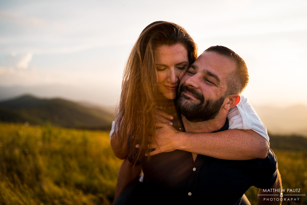engaged couple hugging on mountaintop at sunset