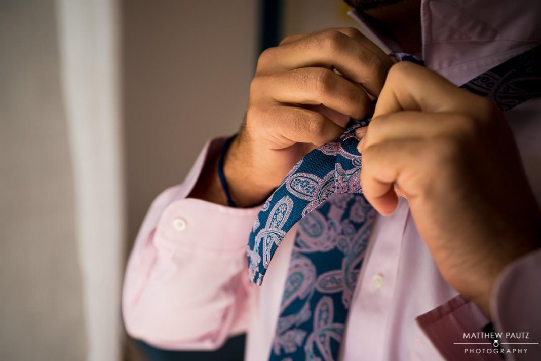 groom tying tie before destination wedding ceremony