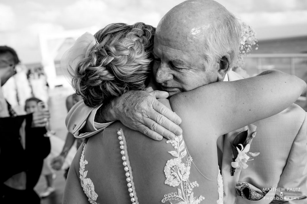 bride hugging father after wedding ceremony