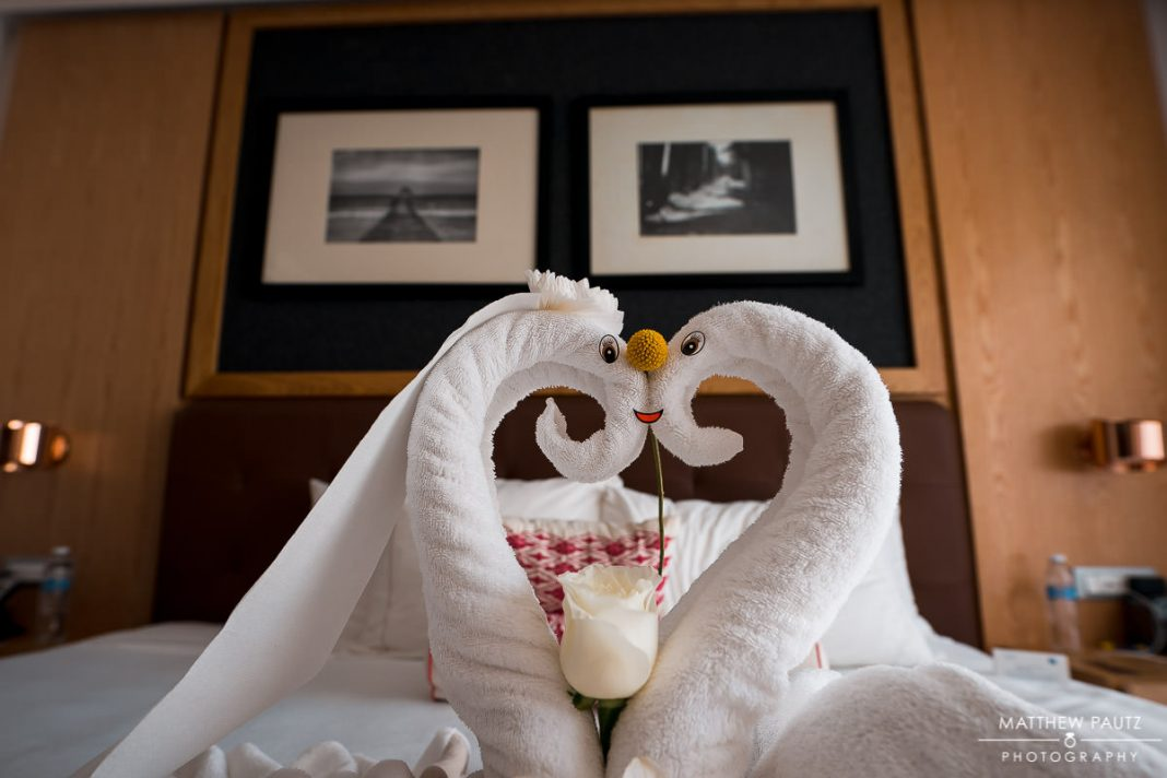 folded towels in shape of swan on resort bed