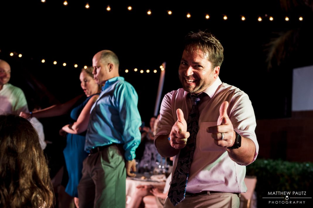 groom giving finger guns at wedding reception
