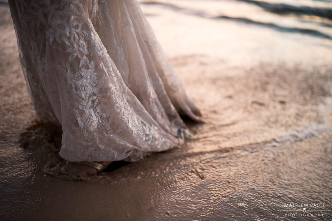 bride standing in surf at destination wedding on beach