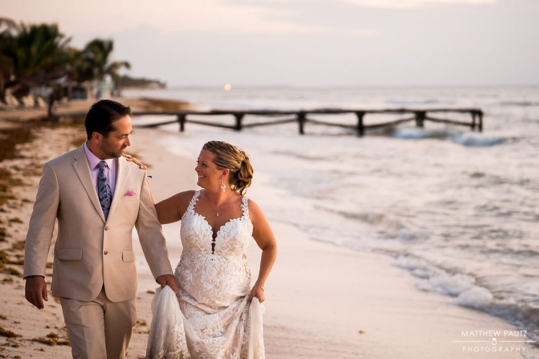 bride and groom walking side by side on beach after destination wedding ceremony