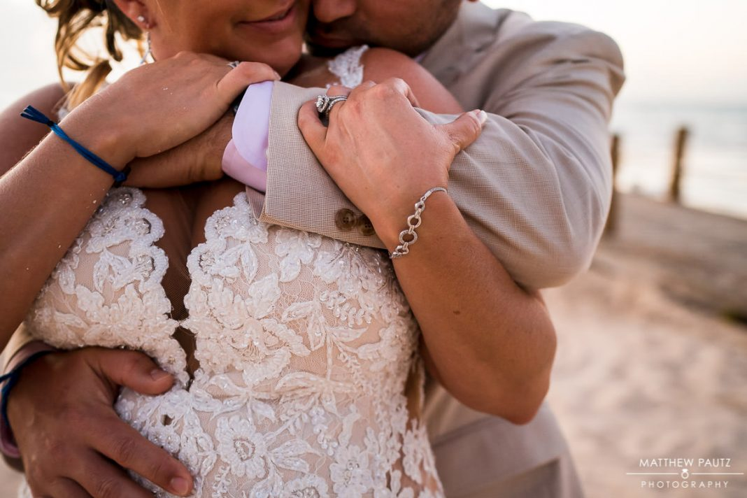 bride and groom hugging after beach wedding