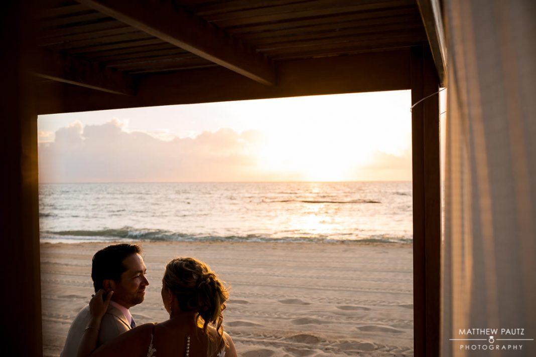 bride and groom enjoying sunrise on beach after destination wedding