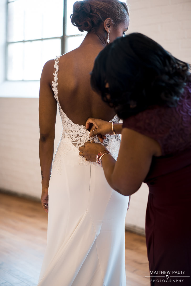 mother of bride helping bride lacing up wedding dress