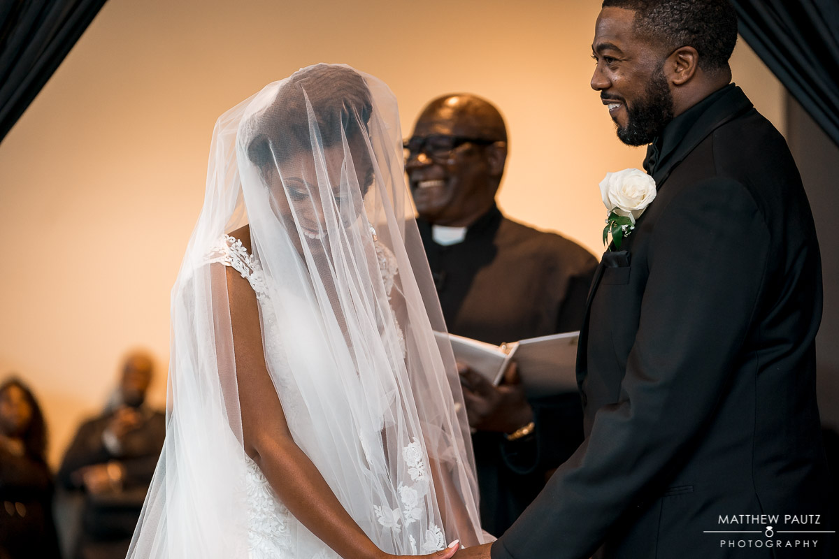 Bride blushes in front of groom at wedding ceremony