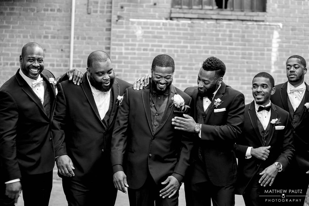 Groomsmen congratulating groom while walking at 701 Whaley