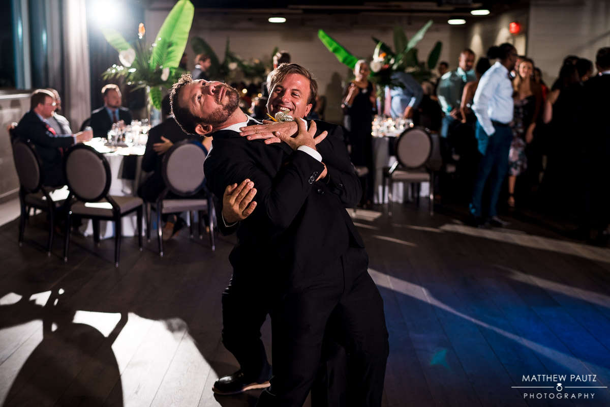 groomsmen dancing together at wedding reception
