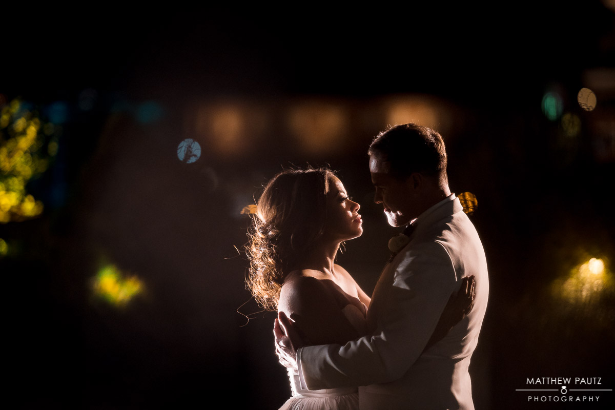 newlywed couple dancing together on rooftop at night after wedding