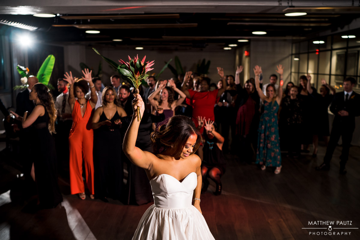 bride throwing wedding bouquet at reception