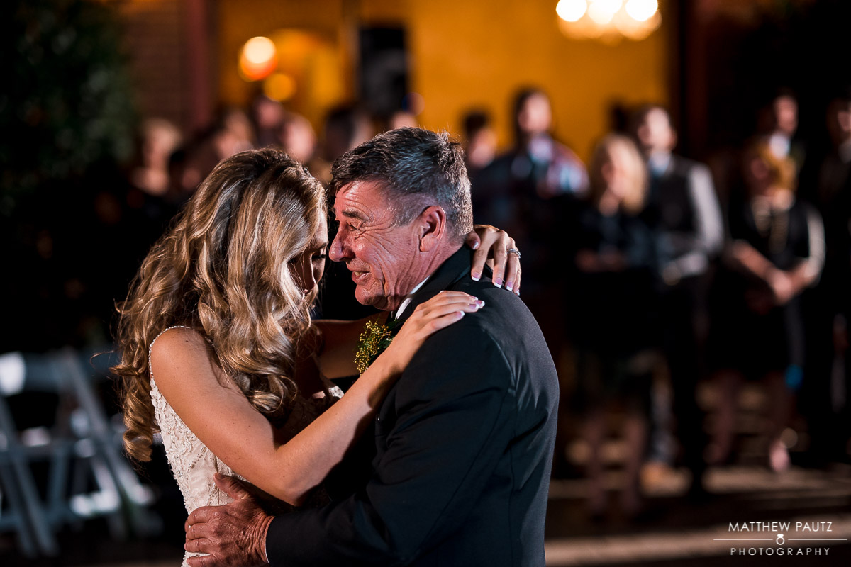 Bride dancing with her father outside at night after wedding ceremony