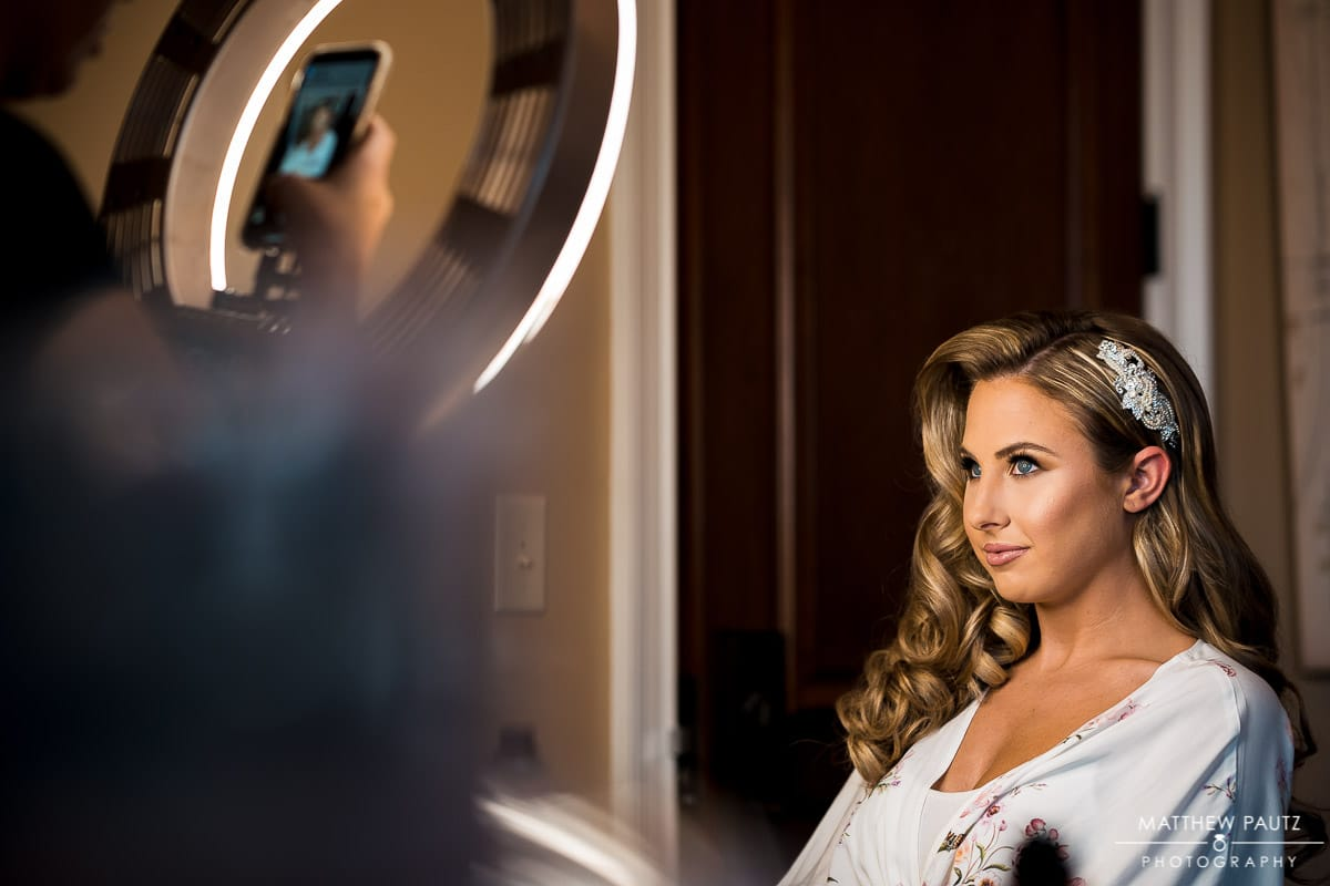 Bride looking at ring light during hair and makeup