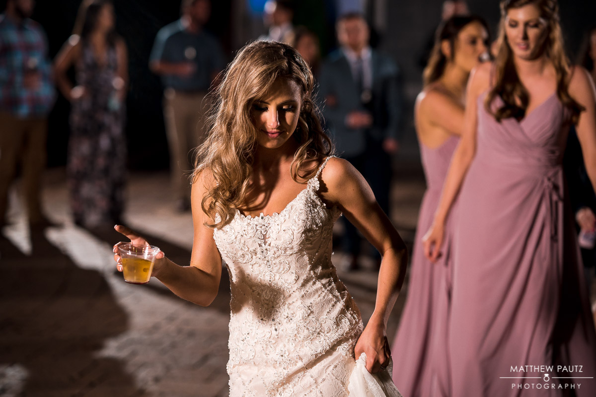 Bride dancing while holding a drink at wedding reception