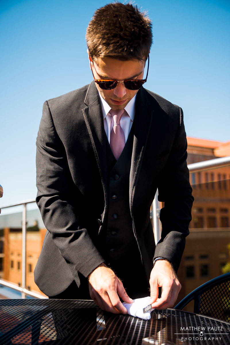 Groomsman tying pocket square before wedding ceremony