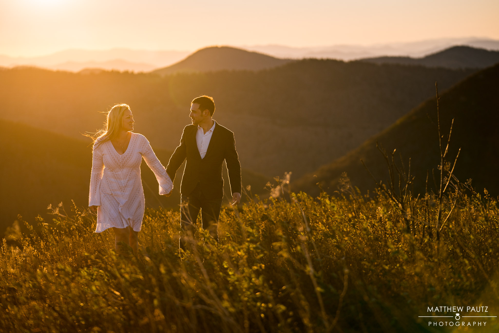 Engaged couple walking together in tall grass at Black Balsam Knob