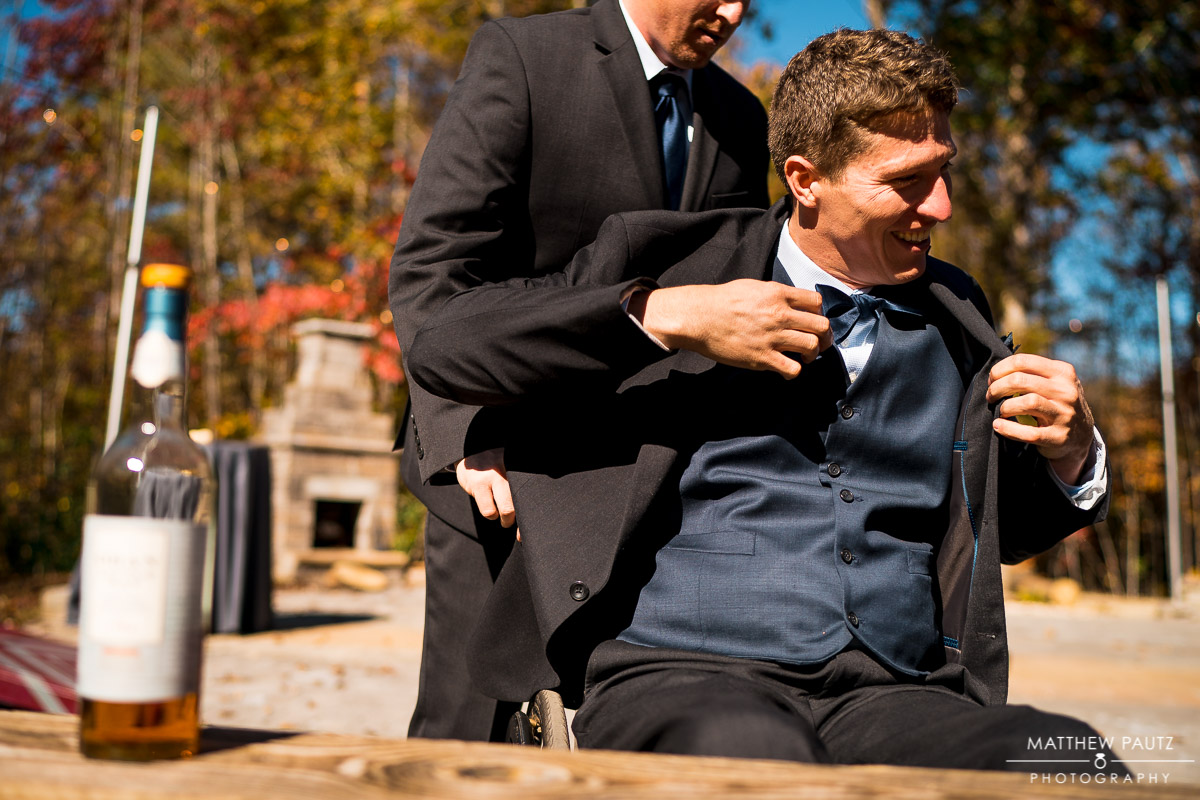 Groom in wheelchair putting on jacket before wedding ceremony