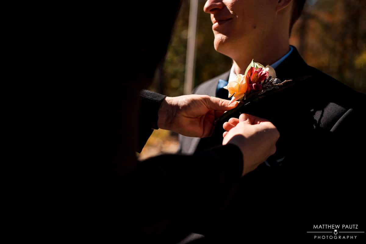 Groom getting boutonniere pinned on jacket for wedding
