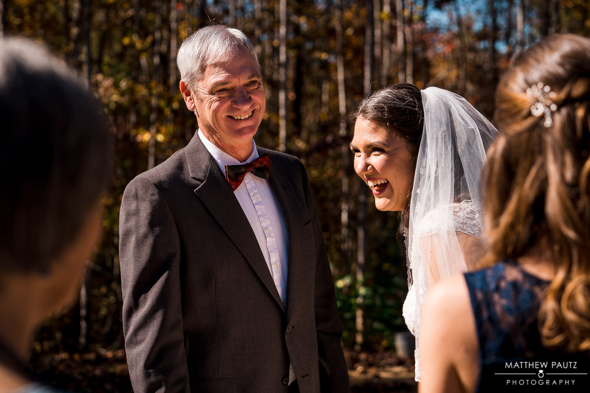 Bride laughing after seeing father before wedding ceremony