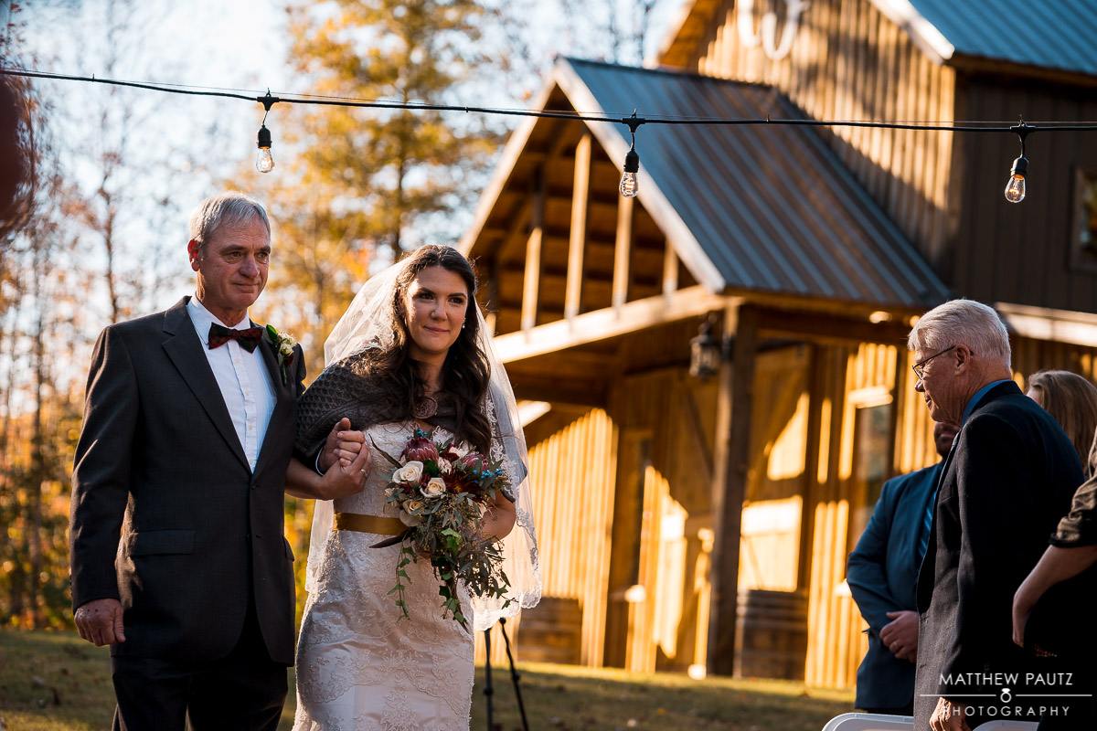 bride walking with her father at outdoor Fall wedding ceremony