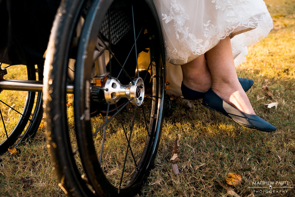 Closeup photo of groom's wheelchair next to bride's shoes