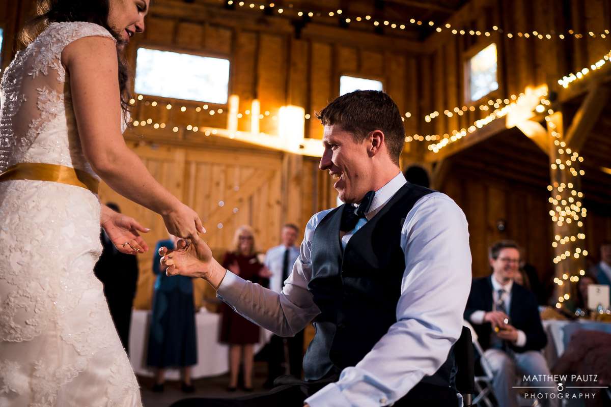 Bride dancing at reception with groom in wheelchair