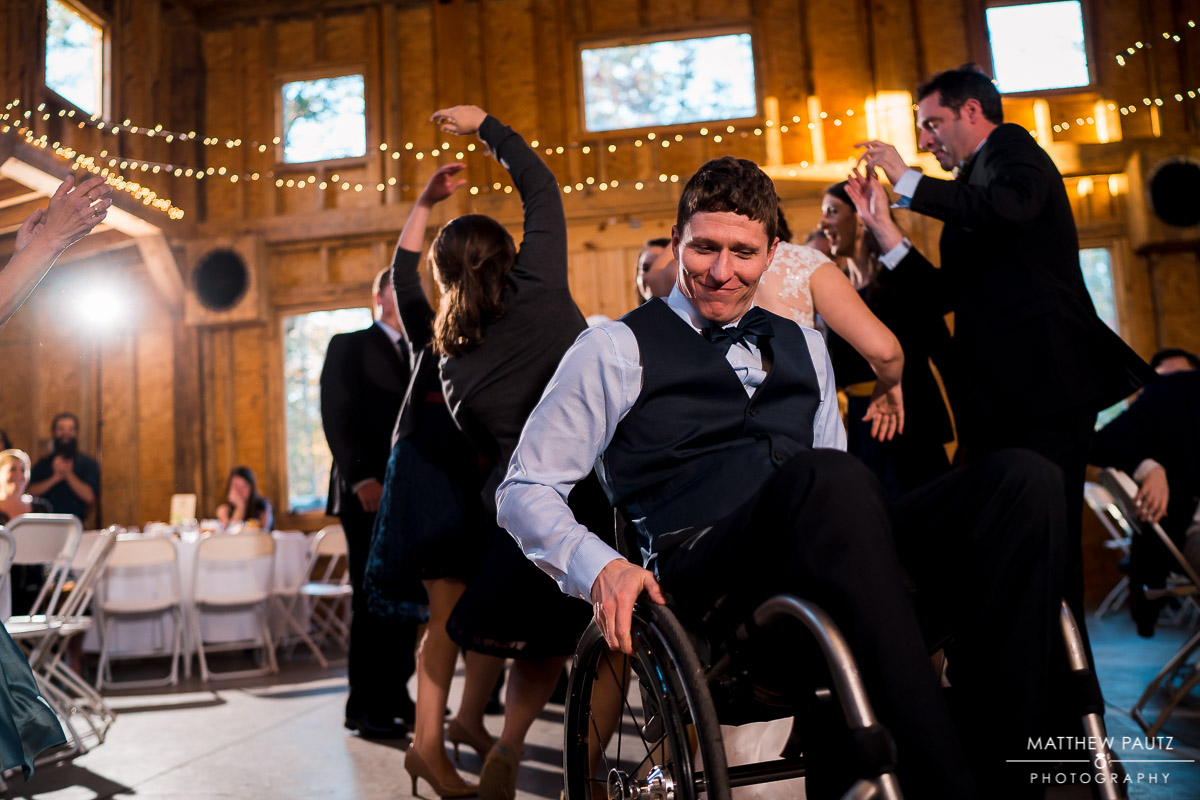 Reception dancing photos with groom in wheelchair