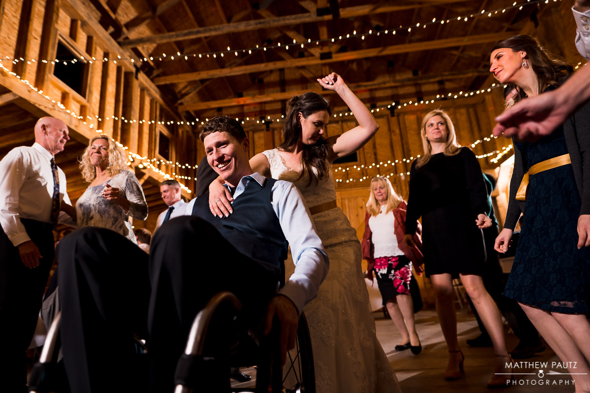 Bride and groom in wheelchair dancing at wedding reception