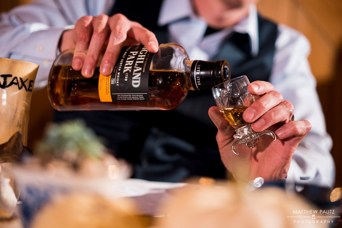 Groom pouring scotch at wedding reception