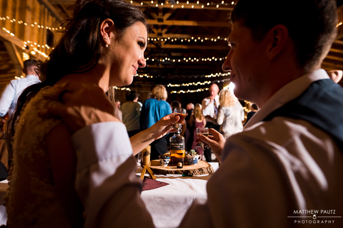 Bride and groom toasting whiskey shots at wedding reception