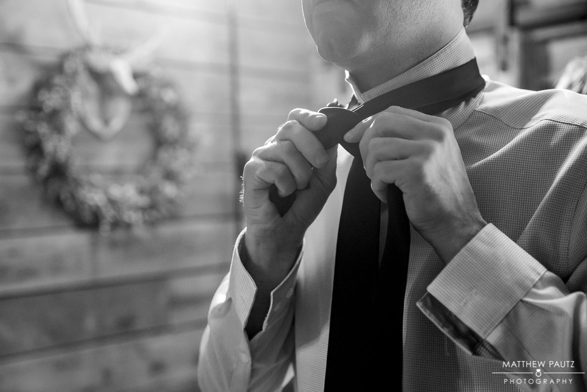 Groomsman tying tie before wedding