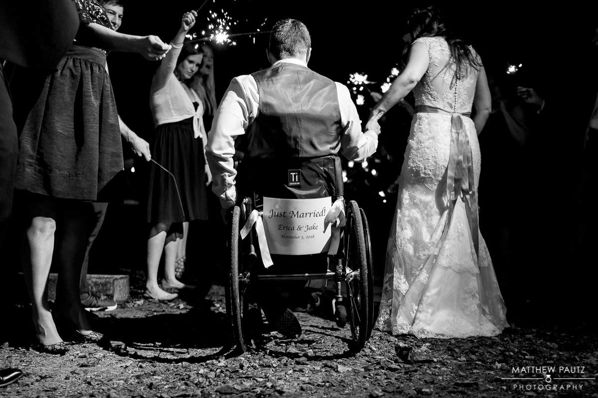 Just married sign on back of groom's wheelchair