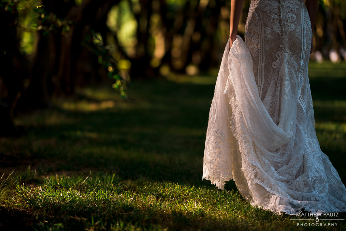 Bride holding up wedding dress while she walks away outside