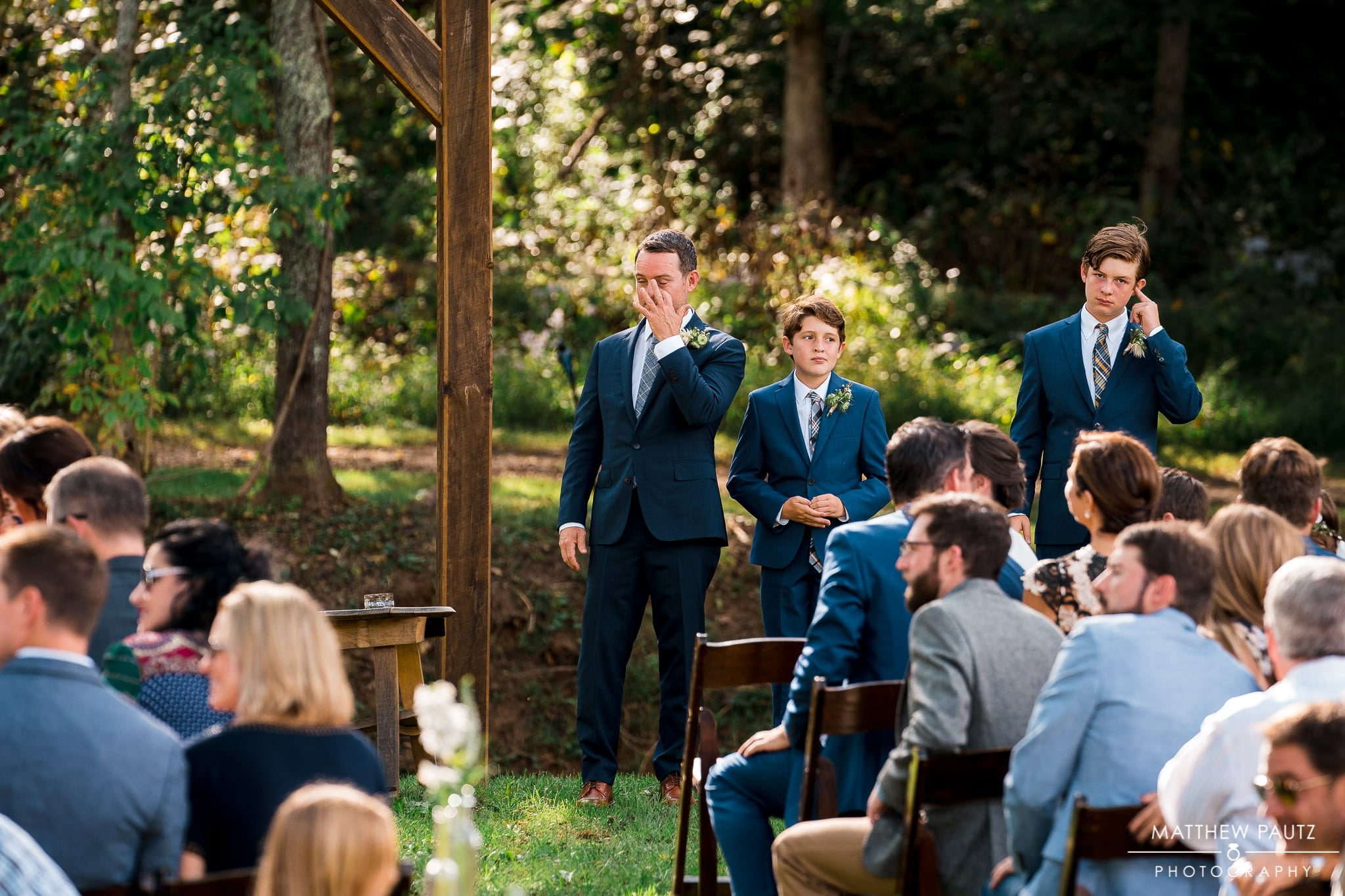 Groom wiping tear from eye after seeing bride at wedding ceremony
