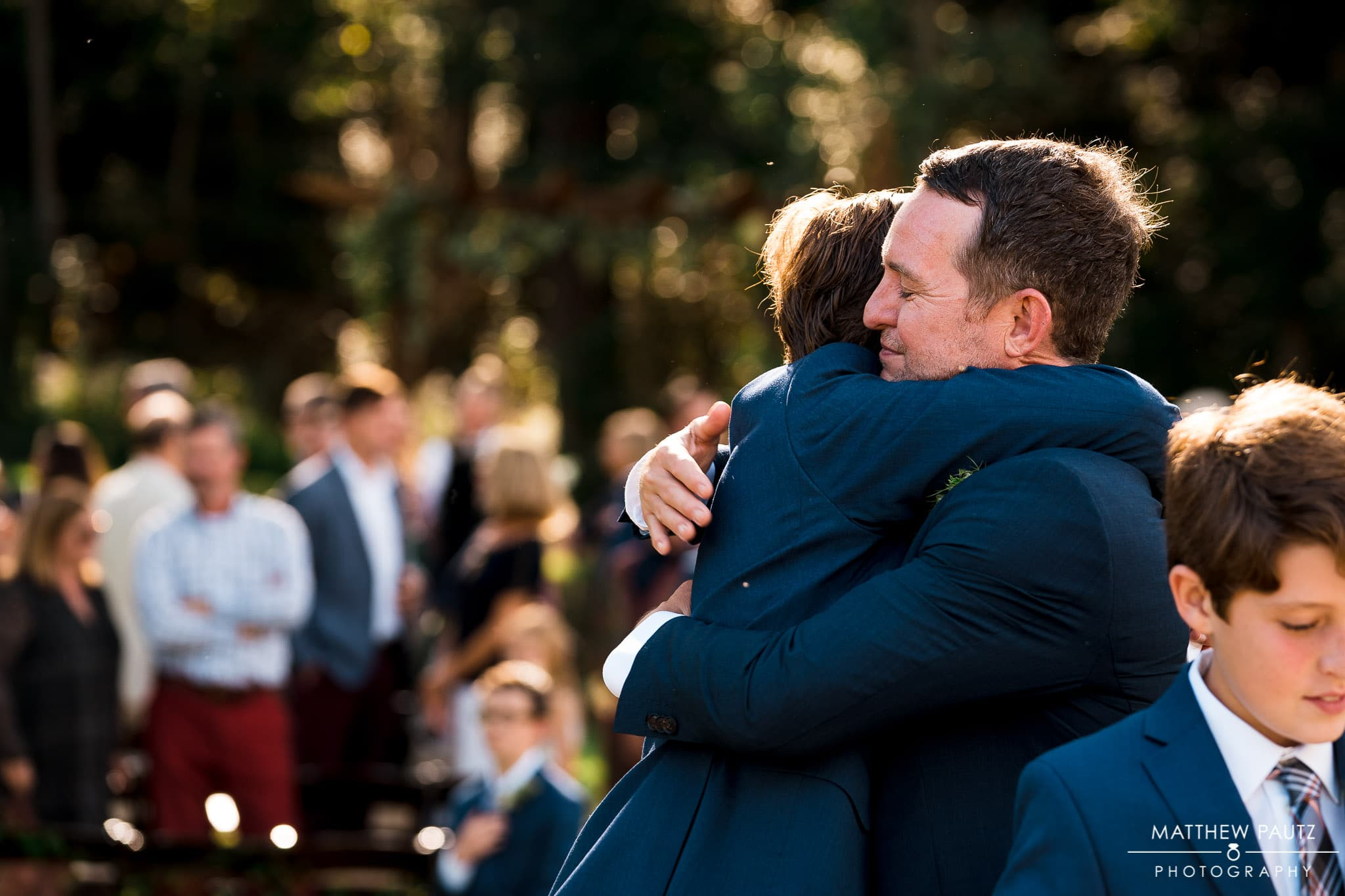 groom hugging son after wedding ceremony