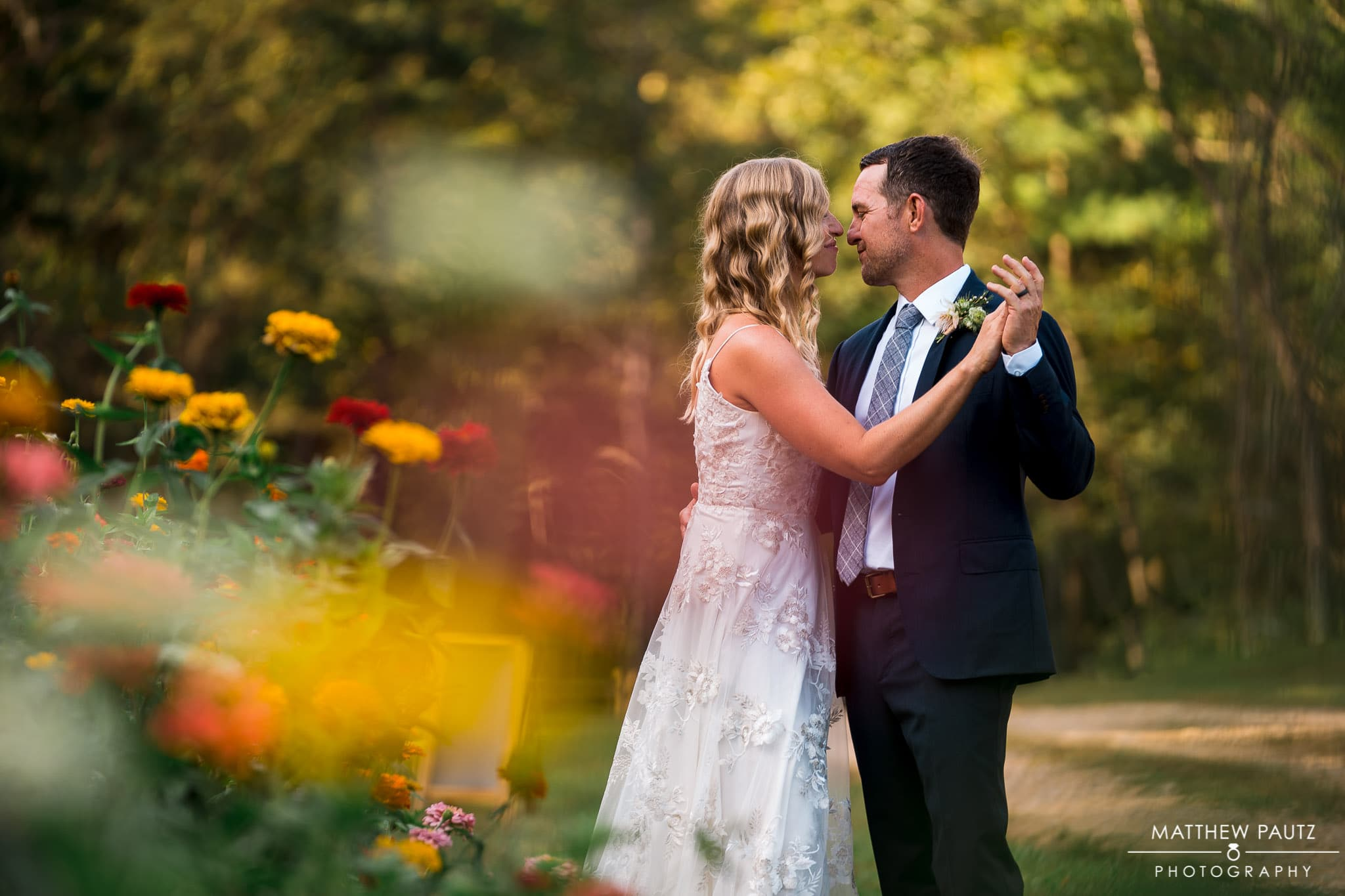 bride and groom dancing in flowers after outdoor wedding in Asheville NC