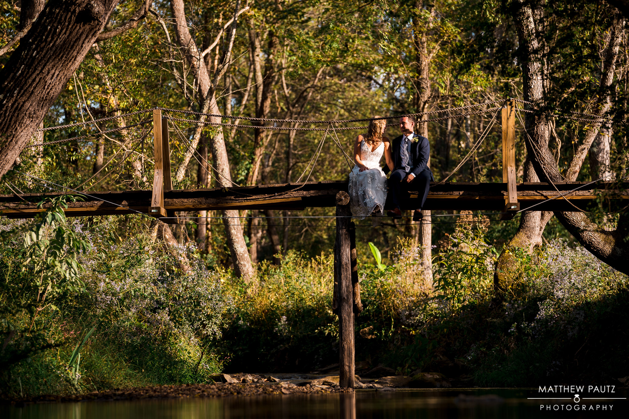 Bride and groom sitting on bridge together after wedding ceremony in Asheville