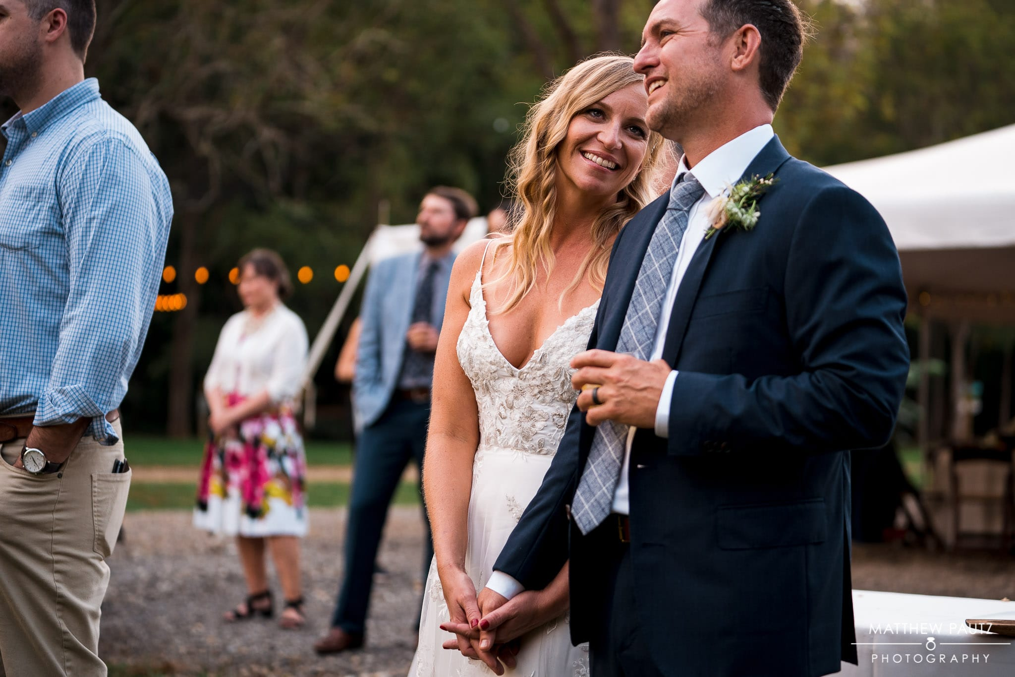 bride and groom listen to family member sing at beginning of wedding reception