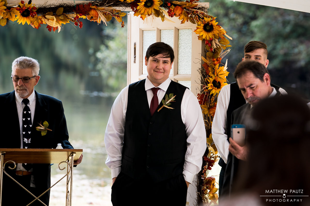 Groom watching bride walk down the aisle at wedding ceremony