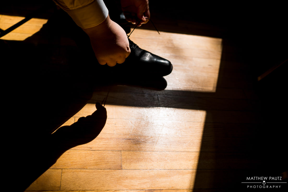Groom tying shoes before wedding ceremony