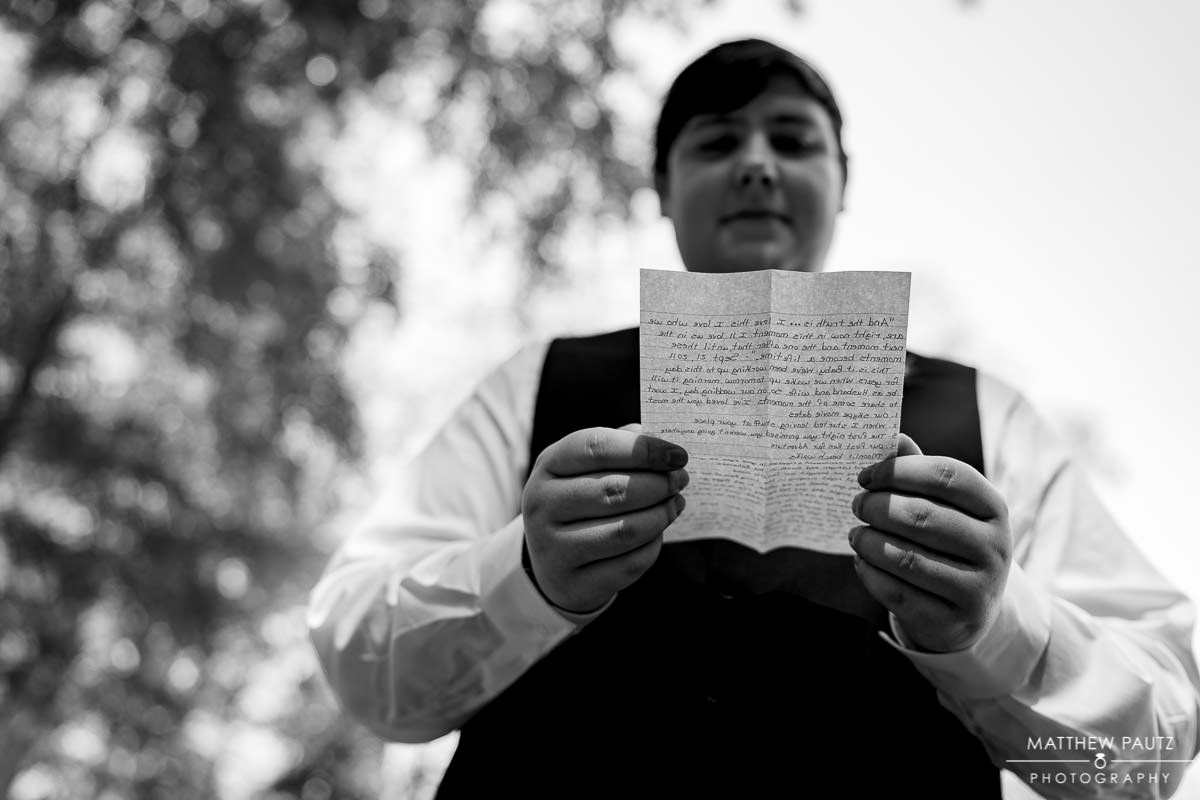 groom reading personal note from bride before wedding