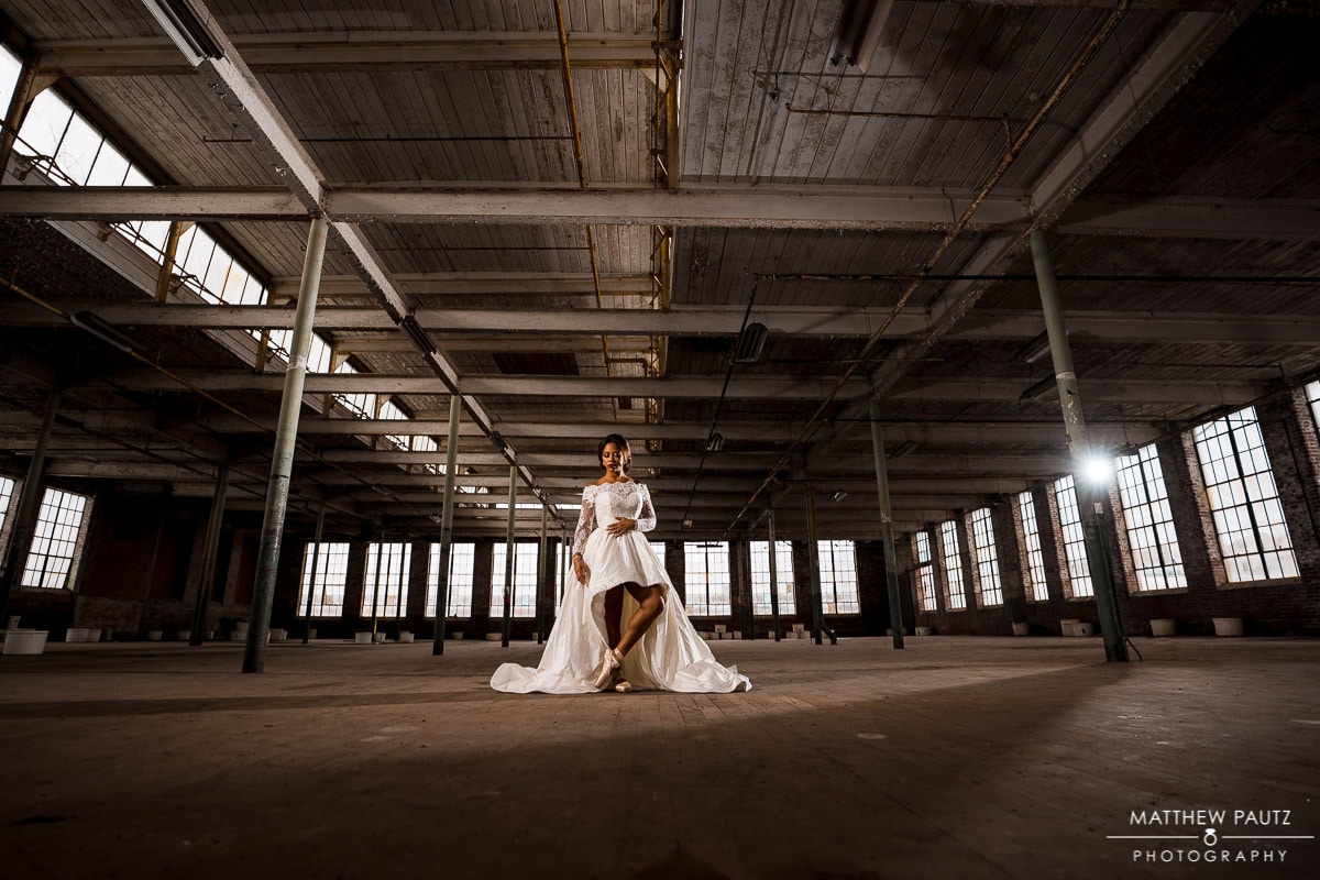Bride posing in wedding dress in an abandoned textile mill