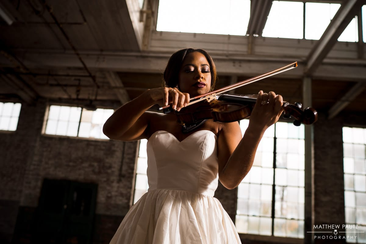 Bride in wedding dress playing violin in old mill building